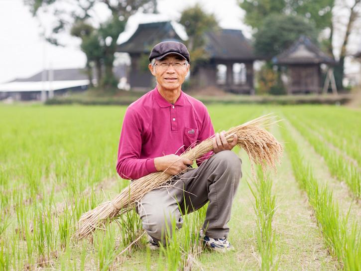 稲刈り後の田んぼに立つ小池裕生さん
