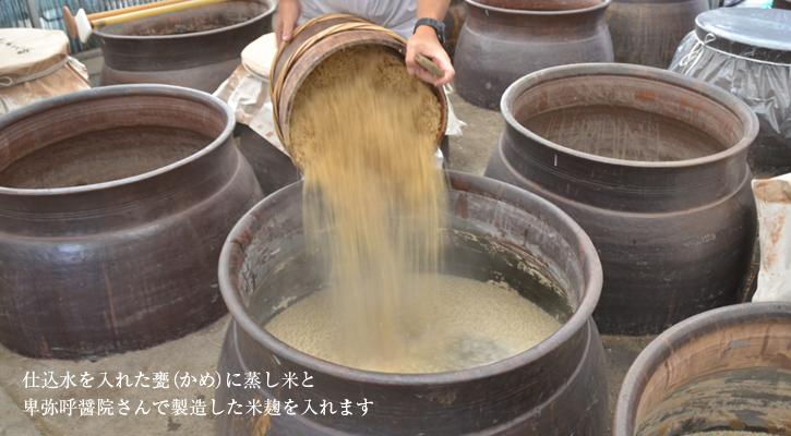 甕に米と麹を入れる